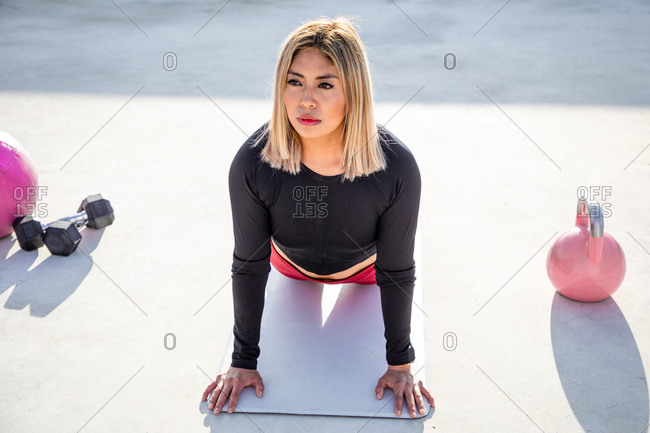 From above blonde haired young woman in sportswear looking away while leaning on straight hands lying on mat on concrete roof of building