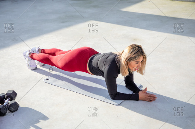 From above of young blonde in stylish active wear in plank position on outdoors roof of building
