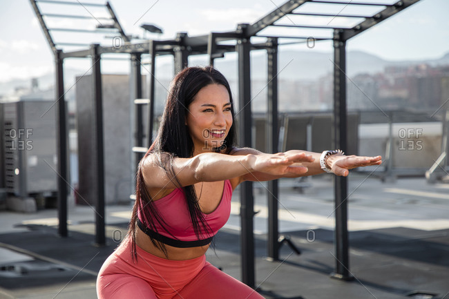 Side view of beautiful focus woman in sportswear jumping on box and squatting while training on rooftop with modern sport equipment in city