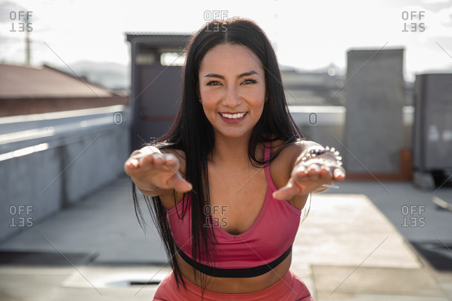 Beautiful focus woman in sportswear jumping on box and squatting while training on rooftop with modern sport equipment in city