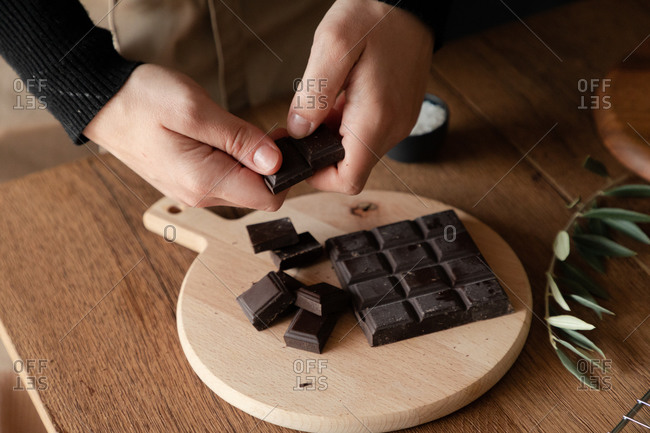 From above of crop hands of housewife breaking chocolate bar over wooden cutting board while preparing dessert at wooden table in home kitchen