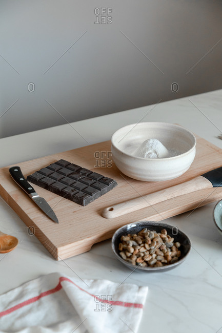 White flour with chocolate and nuts placed on marble table with wooden board and kitchen utensils prepared for pastry recipe