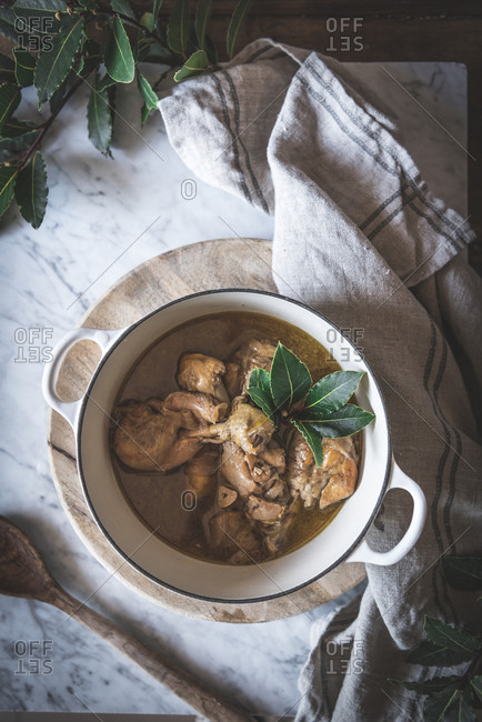 Top view of stewed chicken with broth in pan decorated with green leaves on white marble table
