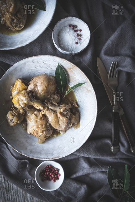 Top view of stewed chicken drumsticks with broth in white ceramic bowl decorated with greenery on table with spices and beverage
