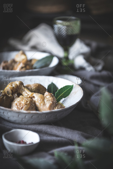 From above stewed chicken drumsticks with broth in white ceramic bowl decorated with greenery on table with spices and beverage