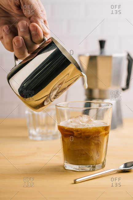 Professional faceless barista pouring milk from metal pitcher in glass with fresh ice coffee on wooden table in cafe