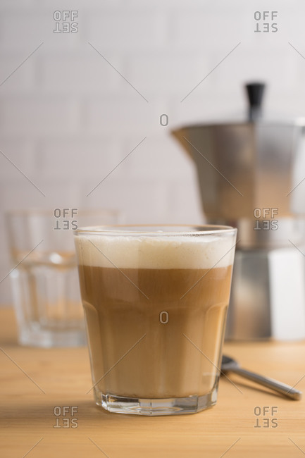 Transparent glass with tasty coffee with milk foam on wooden table with utensil on blurred background