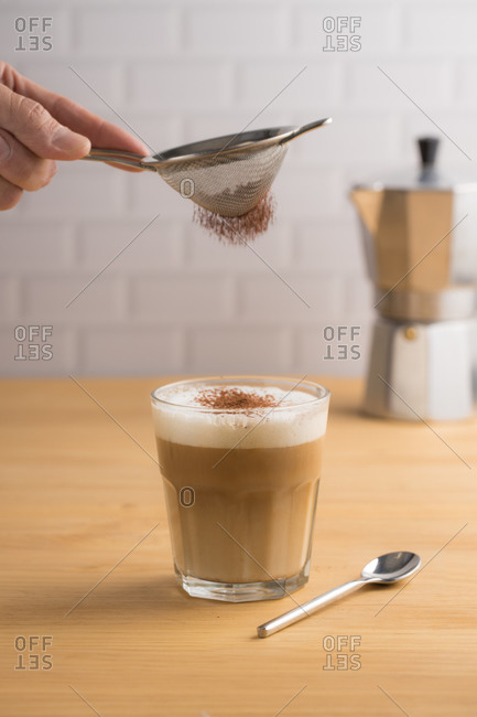 Anonymous barista sifting cacao powder by sieve on glass with brewed coffee and milk foam in cafe