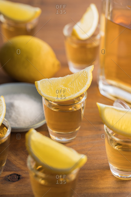 From above glass shots of golden tequila with salty rim and slices of lemon on top on wooden table