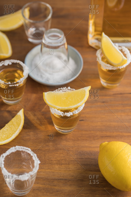 From above top view of glass shots of golden tequila with salty rim and slices of lemon on top on wooden table