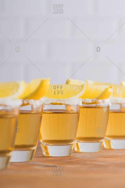 Row of glass sots with golden tequila and slices of lemon on wooden table with white wall on blurred background