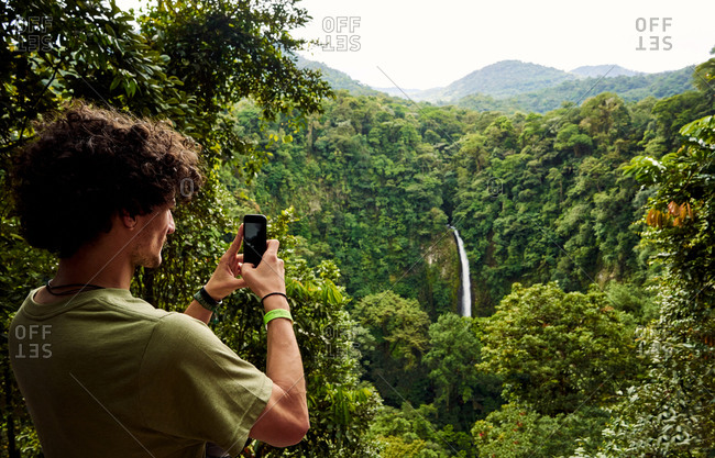 Back view of man with curly hair using smartphone to take photo of waterfall while travelling through green jungle in Costa Rica