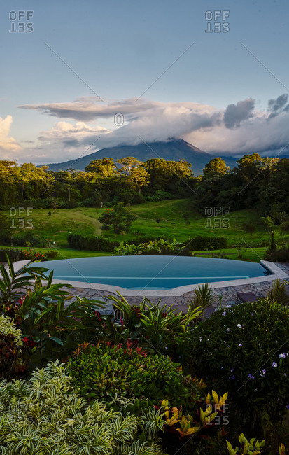 Swimming pool with clean water located near exotic plants in green valley near mountain peak in cloudy evening in Costa Rica