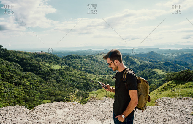 Side view of concentrated male hiker with backpack text messaging on cellphone during trekking  in mountain location in Costa Rica