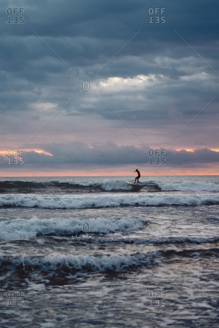 Unrecognizable man with surfboard walking near waving sea in cloudy evening on beach in Costa Rica