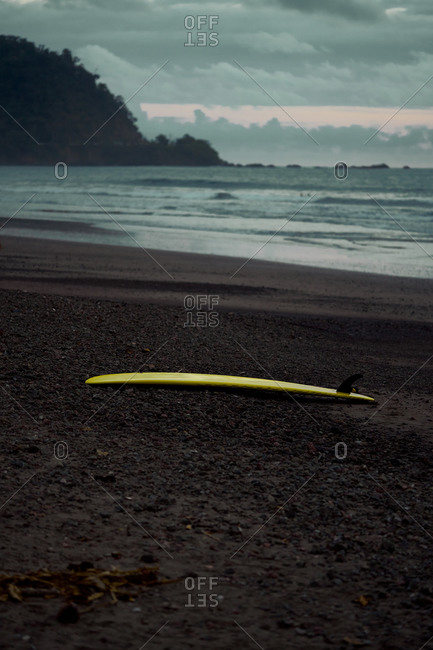 Picturesque scenery of surfboard on sandy beach in twilight in Costa Rica