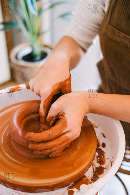 High angle of crop person in casual clothes making handmade pottery using special equipment while working in light contemporary studio