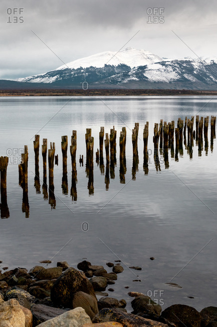 Destroyed wooden pier leading to middle of calm lake against snowy mountain ridge