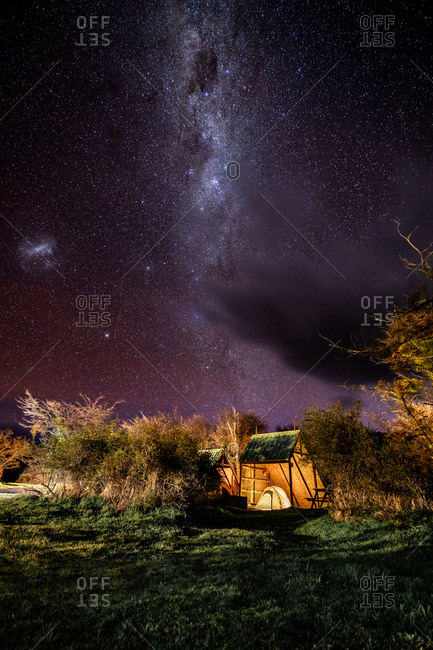 Magnificent scenery with solitary camp on glade among trees under violet clear sky with Milky Way among much of stars