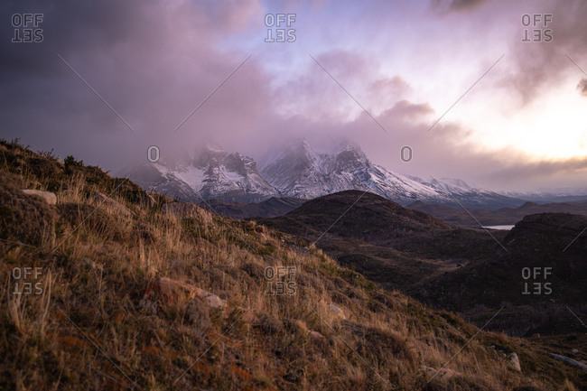 Picturesque landscape of wild highland with snowy mountains peaks and ridges among dramatic clouds during sunset