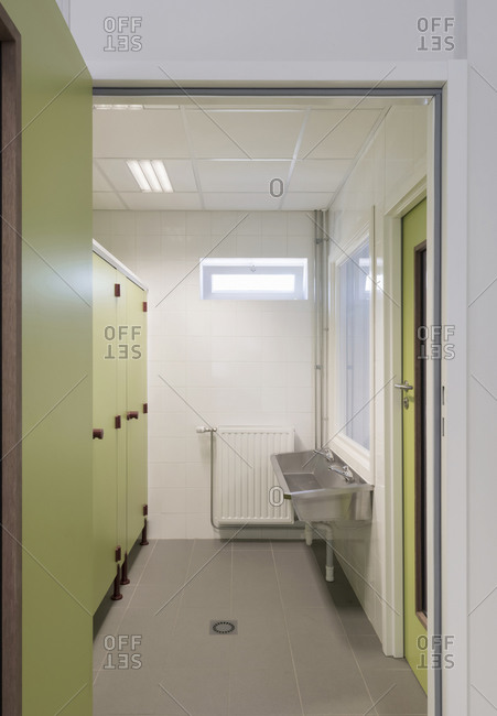 Bathroom interior with green toilet stalls and doors