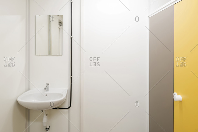 Bathroom interior with one small sink and yellow toilet stall door