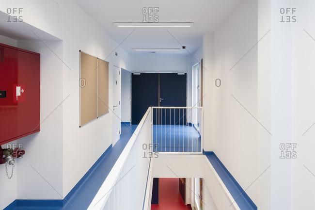 Hallway with blue floors inside a modern school building