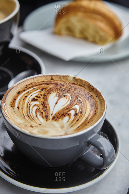 Close up of a cappuccino with croissant in background