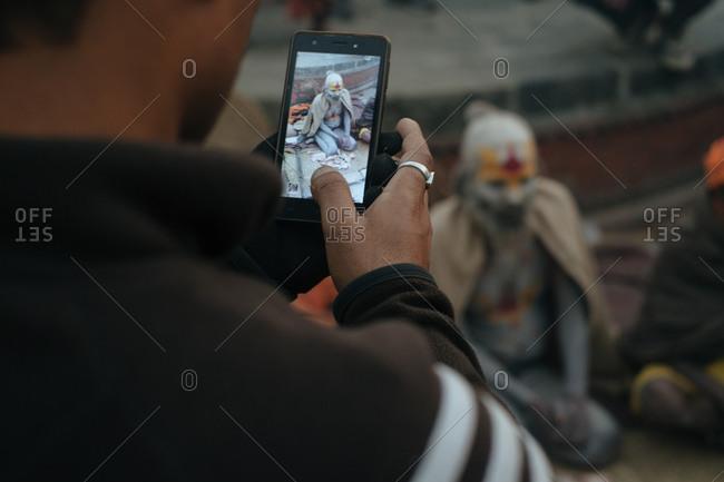 Kathmandu, Nepal - February 24, 2017: Tourists taking photo of man covered in body paint at the Maha Shivaratri festival