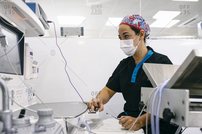 Woman controlling machines and instruments in a veterinary clinic