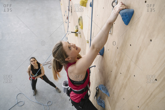 Woman climbing on the wall in climbing gym secured by her partner