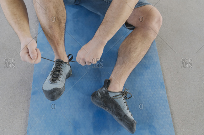Close-up of man putting on climbing shoes