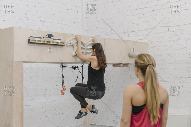 Woman doing pull-ups before climbing