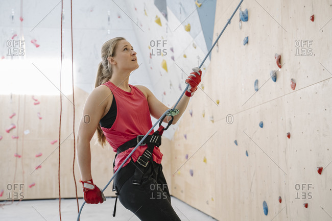 Woman with a rope securing partner on the wall in climbing gym