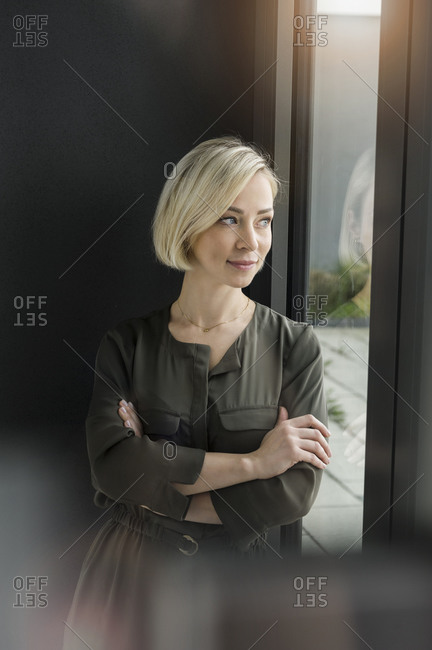 Portrait of content businesswoman looking out of window