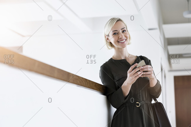 Portrait of smiling businesswoman with mobile phone and handbag