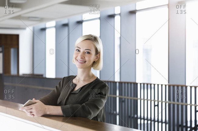 Portrait of happy businesswoman with mobile phone leaning on railing