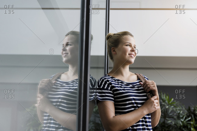 Portrait of a smiling young woman in office reflected in glass pane