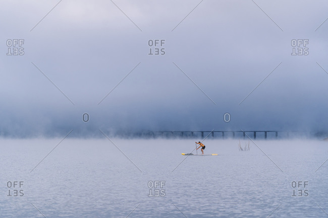 Man stand up paddle surfing on a lake in the fog