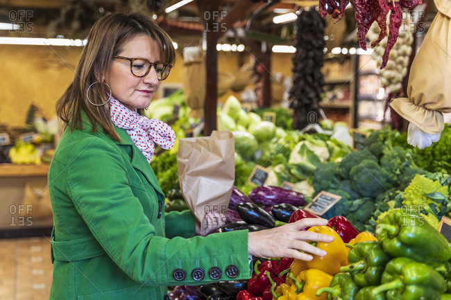Woman shopping for fruit and vegetables in organic shop