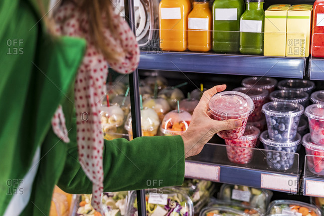 Woman taking packaged berries from cooling shelf in organic store