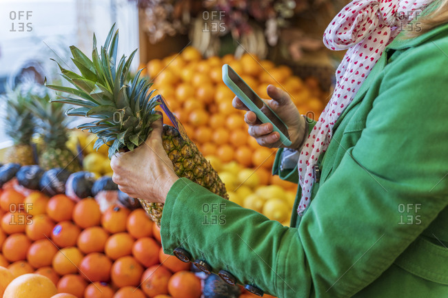 Woman using smartphone app to check a pineapple
