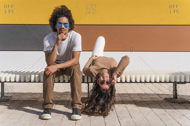 Couple with sunglasses- relaxing on bench- one partner lying on back with head hanging down