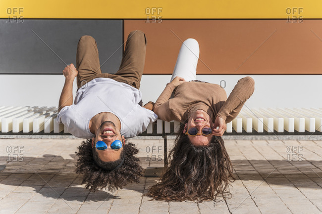 Couple with sunglasses- relaxing on bench- lying on back- heads hanging down