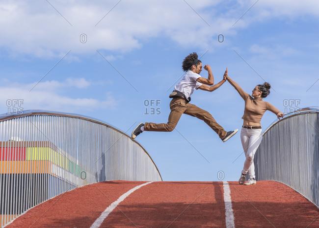 Man jumping mid air on bridge- highfiving woman