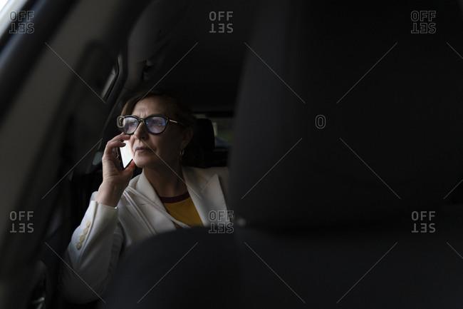 Senior businesswoman sitting in a cab- using smartphone
