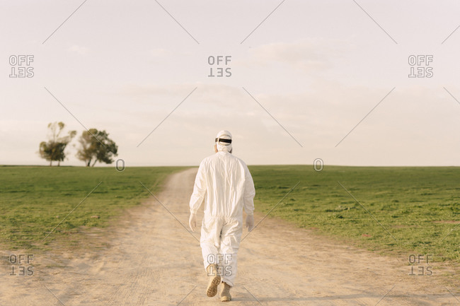 Rear view of man wearing protective suit walking on dirt track in the countryside