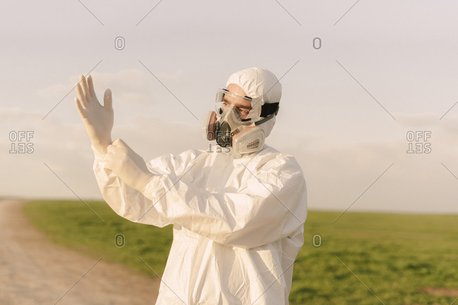 Man wearing protective suit and mask in the countryside putting on protective gloves