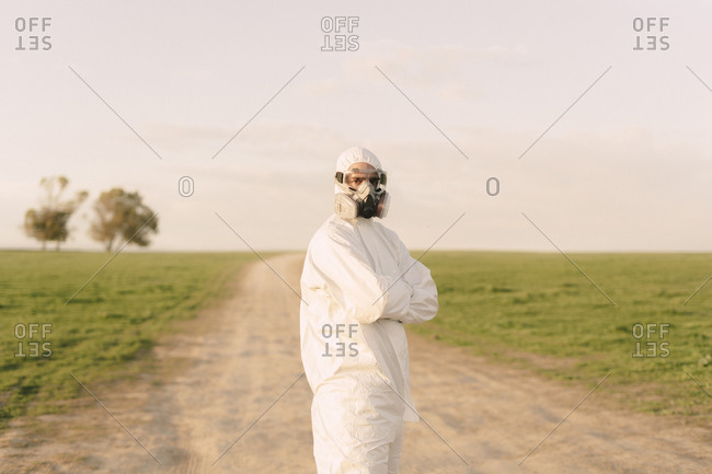 Portrait of man wearing protective suit and mask standing on dirt track in the countryside
