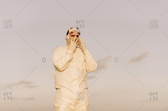 Man wearing protective suit and mask in the countryside